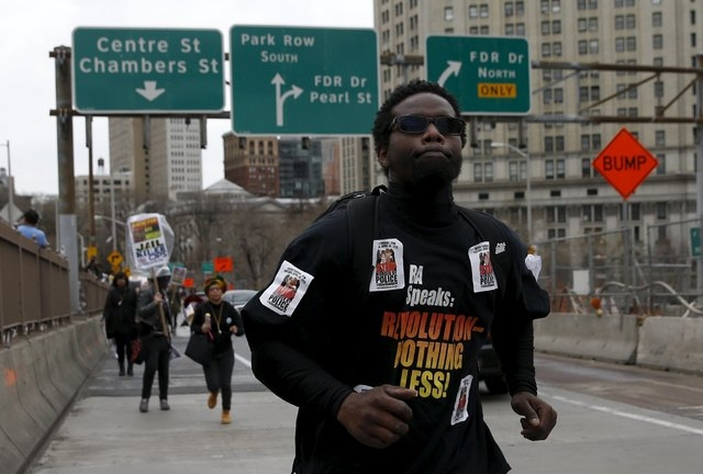 Demonstrators run over the Brooklyn Bridge roadway during a protest against police brutality against minorities in New York, April 14, 2015. Protestors angered by fresh cases of police violence ag ...
