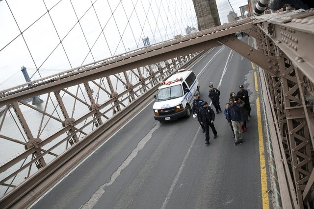 Demonstrators are escorted by the NYPD off the Brooklyn Bridge roadway during a protest against police brutality against minorities in New York, April 14, 2015. Protestors angered by fresh cases o ...