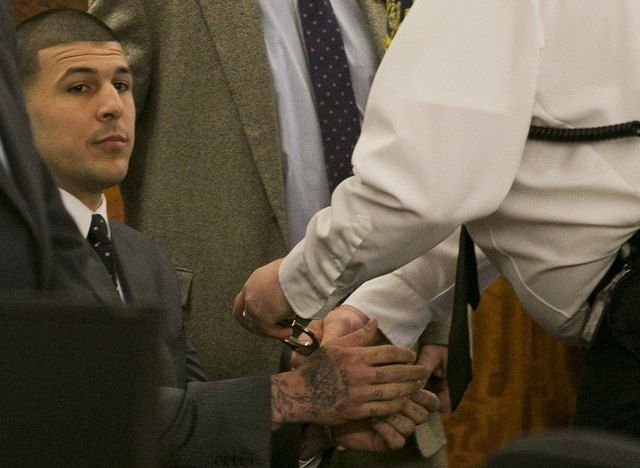 A court officer places handcuffs on the wrists of former NFL player Aaron Hernandez after the guilty verdict was read during his murder trial at the Bristol County Superior Court in Fall River, Ma ...