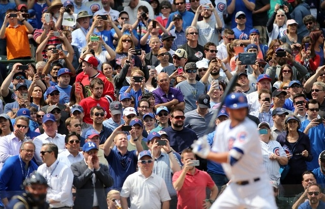 Apr 17, 2015; Chicago, IL, USA; Fans take photos with their cell phones and cameras as Chicago Cubs infielder Kris Bryant comes up to bat during the first inning against the San Diego Padres at Wr ...