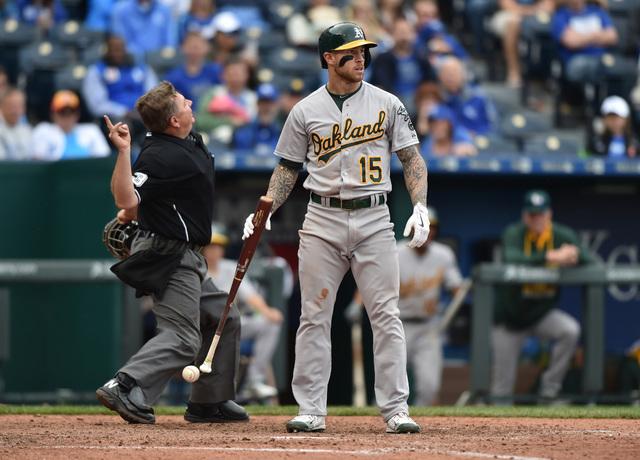 Apr 19, 2015; Kansas City, MO, USA; Oakland Athletics third basemen Brett Lawrie (15) reacts to a high and inside pitch, as home plate umpire Greg Gibson (left) throws Kansas City Royals pitcher K ...
