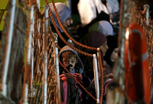 A child looks on as he arrives with migrants on a boat at the Sicilian harbor of Pozzallo April 19, 2015. (Alessandro Bianchi/Reuters)