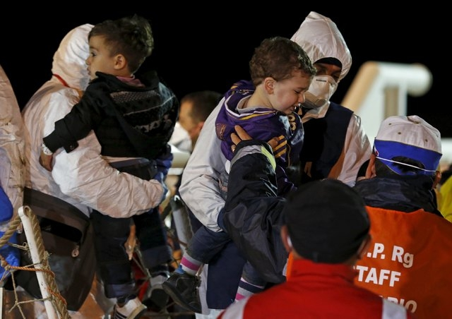 Children are carried by rescue workers as migrants arrive via boat at the Sicilian harbor of Pozzallo April 19, 2015.  (Alessandro Bianchi/Reuters)