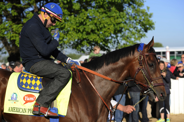Apr 28, 2015; Louisville, KY, USA; Exercise rider Jorge Alvarez makes the sign of the cross before working out  Kentucky Derby hopeful American Pharoah at Churchill Downs. Mandatory Credit: Jamie  ...