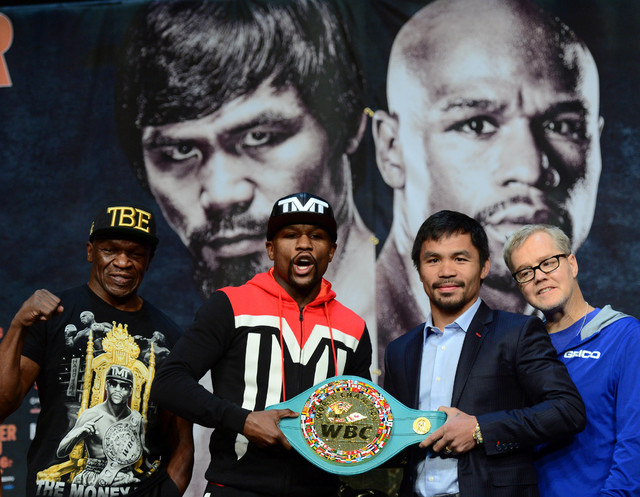 Apr 29, 2015; Las Vegas, NV, USA; Flanked by Floyd Mayweather Sr. (left) and Freddie Roach (right) Floyd Mayweather and Manny Pacquiao pose with a custom WBC belt during a press conference at KA T ...