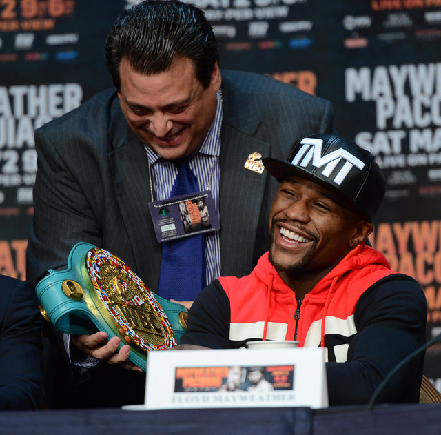 Apr 29, 2015; Las Vegas, NV, USA; WBC president Mauricio Sulaiman shows off a custom belt to Floyd Mayweather during a press conference at KA Theatre. (Joe Camporeale-USA TODAY Sports)