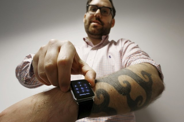 Reuters journalist Matt Siegel inputs his passcode onto his Apple Watch as his tattoos prevent the device's sensors from correctly detecting his skin, in Sydney, Australia, April 30, 2015.  (REUTE ...
