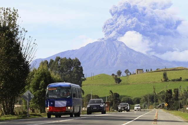 Vehicles travel along a road as smoke and ash rise from the Calbuco volcano as seen from Puerto Varas, Chile, April 30, 2015. Chilean volcano Calbuco, which erupted twice last week, began sending  ...