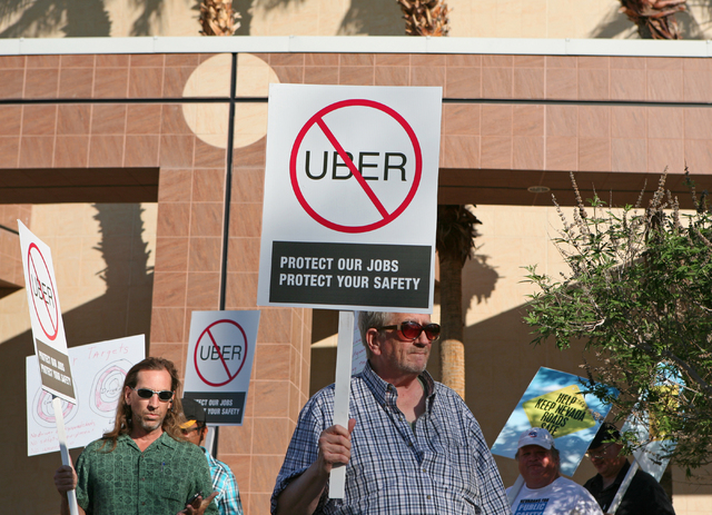 Protestors hold signs outside Grant Sawyer Building Monday, March 30, 2015, in Las Vegas. Dozens of Southern Nevada taxi drivers and supporters rallied to protest a proposed legislation that would ...