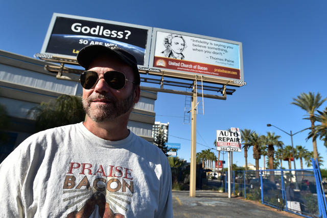 John Whiteside stands under a pair of billboards that support his religious views along Las Vegas Boulevard near Charleston Boulevard on Monday, April 13, 2015. Whiteside, who founded the United C ...