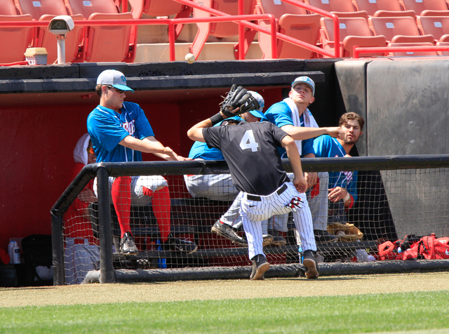 UNLV Rebels freshman Austin Anderson (4) collides with the Lobos dugout barrier, while trying to catch a foul ball during a baseball game with the UNLV Rebels against the University of New Mexico  ...