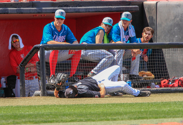 UNLV Rebels freshman Austin Anderson (4) lays on the ground after running into the dugout barrier while attempting to catch a foul ball during a baseball game with the UNLV Rebels against the Univ ...