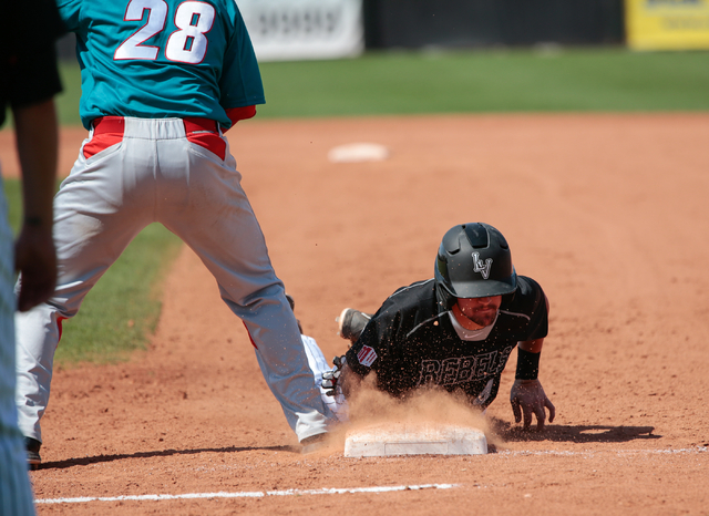 UNLV Rebels freshman Austin Anderson (4) dives back to first base, while trying to avoid being tagged out by first baseman University of New Mexico sophomore Jack Zoellner (28), during a baseball  ...