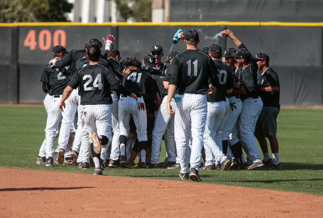 UNLV Rebels senior Edgar Montes (26), not viewed, is surrounded by his teammates and splashed with water after hitting the game winning bunt in the tenth inning during a baseball game with the UNL ...