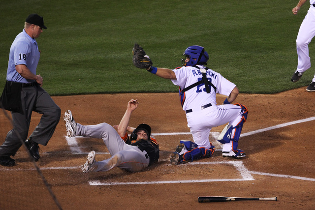 Las Vegas 51s catcher Kevin Plawecki holds up the ball as Fresno Grizzlies Nolan Fontana slides in for a run during the 51s home opener Friday, April 17, 2015, at Cashman Field. (Sam Morris/Las Ve ...