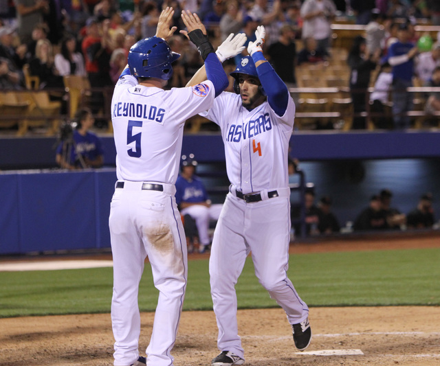 Las Vegas 51s Alex Castellanos, right, is greeted by Matt Reynolds after Castellanos hit a two run homer against the Fresno Grizzlies during the 51s home opener Friday, April 17, 2015, at Cashman  ...