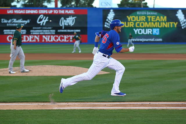 Kris Bryant of the Chicago Cubs runs to first base against the Oakland Athletics during the Big League Weekend exhibition baseball game at Cashman Field in Las Vegas on Friday, March 13, 2015. (Ch ...