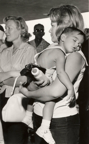 A woman hold a toddler as she waits in line to purchase concert ticket to see the British rock 'n' roll band The Beatles at the Las Vegas Convention Center, June 29, 1964. (Terry Todd/Las Vegas Re ...