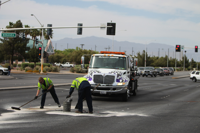 Tow truck drivers clean debris after a four vehicle car accident at the intersection of Bonanza Road and Pecos Road in Las Vegas Sunday, April 5, 2015. (Erik Verduzco/Las Vegas Review-Journal)