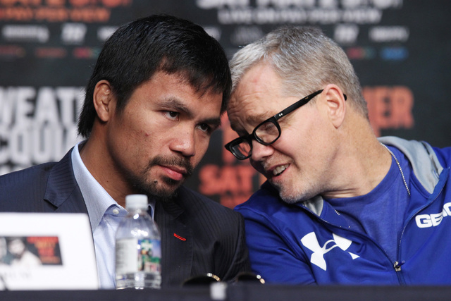 Manny Pacquiao listens to trainer Freddie Roach during the final news conference for his fight against Floyd Mayweather Jr. Wednesday, April 29, 2015 in the Ka Theater at the MGM Grand. (Sam Morri ...