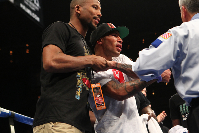 Ashley Theophane, center, celebrates his victory over Mahonri Montes, not pictured, in their junior welterweight fight at The Pearl at the Palms hotel-casino in Las Vegas on Thursday, April 30, 20 ...