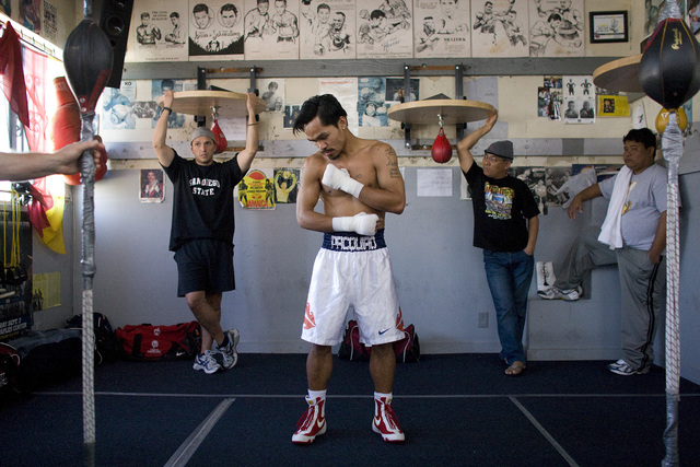 Manny Pacquiao warms up before a workout at the Wild Card Boxing Gym in Hollywood, Calif. Nov. 12, 2008. Around him are people in his training camp. (John Locher/Las Vegas Review-Journal)