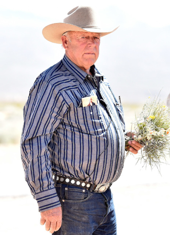 Rancher Cliven Bundy carries a bouquet of desert foliage that his cattle grazes on during an event near his ranch in Bunkerville on Saturday, April 11, 2015.  Bundy is hosting the event celebratin ...