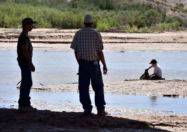Parents watch over their children play along the Virgin River during an event at the Bundy Ranch in Bunkerville on Saturday, April 11, 2015. Rancher Cliven Bundy is hosting barbecue celebrating th ...