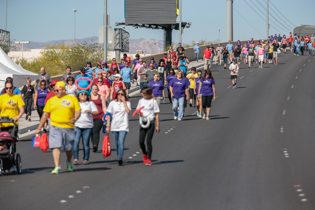 A crowd of participants walk back across the overpass on West Sunset road as part of the course for the Aid for AIDS of Nevada (AFAN) hosts the 25th Annual AIDS Walk Las Vegas at Town Square Las V ...
