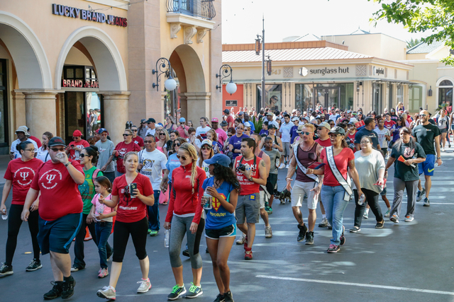 A large crowd of participants walk along the course through the streets of Town Square during the Aid for AIDS of Nevada (AFAN) 25th Annual AIDS Walk Las Vegas at Town Square Las Vegas, South Las  ...
