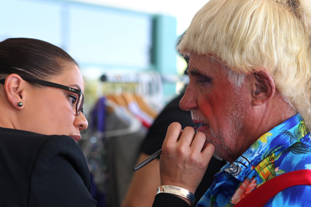 Makeup artist Bernicia Carreira, left, works with Ray Lavallee as he gets ready for his drag queen outfit for the Guinness World Records largest drag queen stage show event at Hard Rock Cafe in La ...