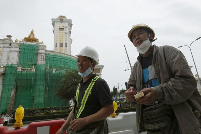 Workers from mainland China walk outside the new phase of Galaxy Macau, which is under construction, during a lunch break in Macau 17, 2015. Macau is drafting new construction safety rules, offici ...