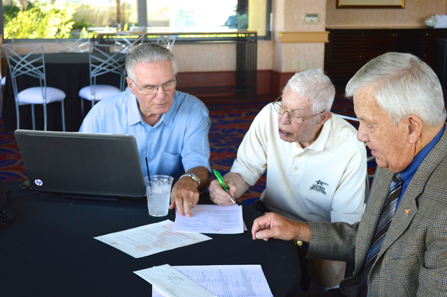 Gary Duffel, left, and Favil West, right, of the nonprofit Foundation Assisting Seniors, help Bob Brill sign up for the HowRU Program in September 2014. Brill was the program's first participant,  ...