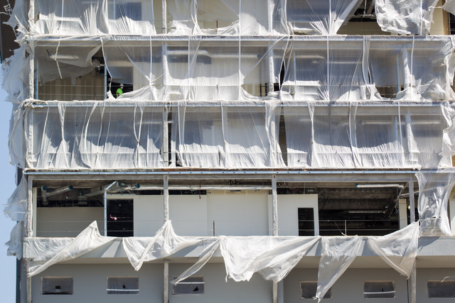 A construction worker is seen as plastic sheets blow in the wind at the Federal Justice Tower, under construction at 501 Las Vegas Blvd. in downtown Las Vegas on Tuesday, April 14, 2015. (Chase St ...