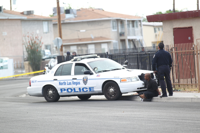 A man is seen detained as North Las Vegas police investigate the scene of a shooting that left one person in critical condition in the 2500 block of Las Vegas Boulevard North on Tuesday, April 14, ...