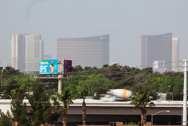 Traffic moves along U.S. Highway 95 near Boulder Highway as the Strip is seen partially obscured by dust in the background in Las Vegas on April 1, 2015. The Clark County Department of Air Quality ...