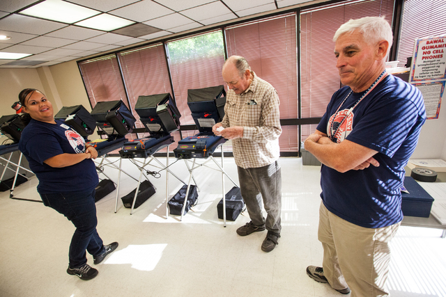 Glen Dunning, center, briefly chats with election workers Karina Mota, left, and team leader Steven Moran at a polling place for the municipal election at the Las Vegas Senior Center at 451 E. Bon ...