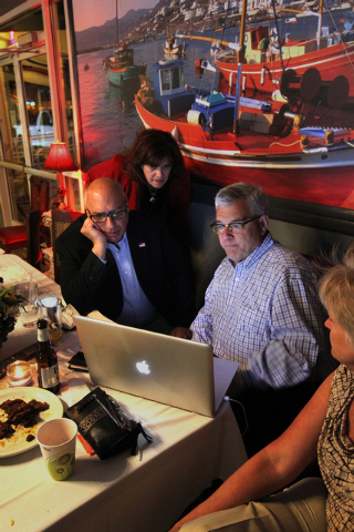 Las Vegas City Councilman Stavros Anthony and his co-campaign managers Lisa Mayl and Steve Forsythe look at a computer as the final results come in for his bid to unseat Las Vegas Mayor Carolyn Go ...