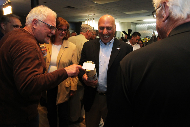 Las Vegas City Councilman Stavros Anthony receives a gift of a bottle of ouzo from a supporter during an election night party at Mykonos Greek restaurant Tuesday, April 7, 2015. (Sam Morris/Las Ve ...