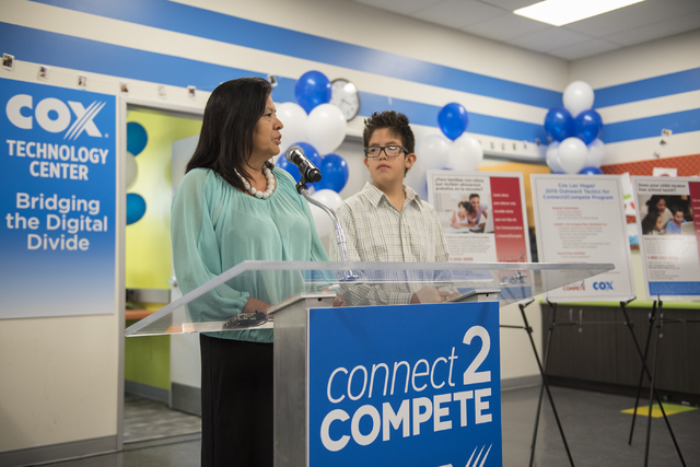 Margarita Gonzalez and her son Michael, 11, speak to the news media during an announcement for the Connect2Compete program at a ribbon cutting ceremony for the Cox Technology Center at Desert Pine ...