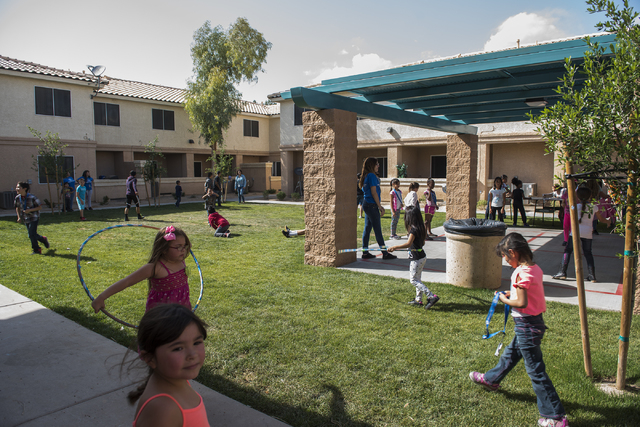 Community kids play outside the Desert Pines Boys & Girls club during an announcement for the Connect2Compete program at a ribbon cutting ceremony for the Cox Technology Center at Desert Pines Boy ...