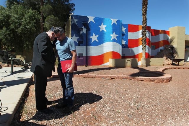 American Legion chaplain Rev. Brian Wallace says a prayer for artist Scott LoBaido after a ceremony to thank Lobaido for the U.S. flag that he painted on the side of American Legion Post 8 Wednesd ...