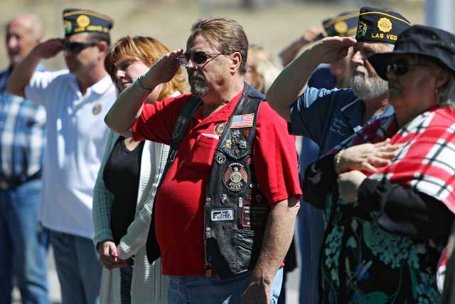 Veterans and supporters salute during the national anthem before a ceremony to thank artist Scott Lobaido for the U.S. flag that he painted on the side of American Legion Post 8 Wednesday, April 8 ...