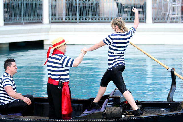 Tino Fortuna, center, assists a drenched gondolier candidate after her required plunge into the frigid waters of the Grand Canal at The Venetian hotel-casino on Friday, April 3, 2015. (Michael Qui ...