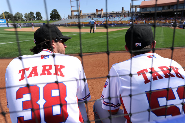 Fresno Grizzlies pitchers Darin Downs (38) and Jordan Jankowski are seen in the bullpen sporting special jerseys honoring the late Fresno State and UNLV head basketball coach Jerry Tarkanian durin ...