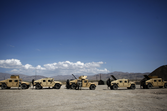 Nevada Army National Guard troops stand next to HMMWVs [common pronunciation Humvee] after participating in a convoy scenario during a pre-deployment drill at the North Las Vegas Readiness Center  ...