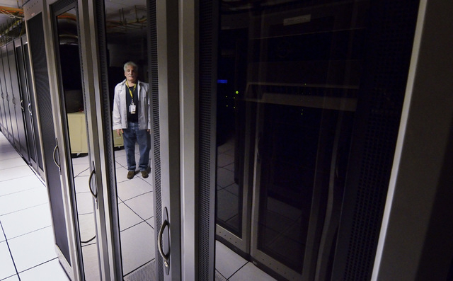 Richard Gray, network supervisor for Clark County information technology, is shown reflected in the glass of one of the server cabinets in the computer room at the government data center on Friday ...