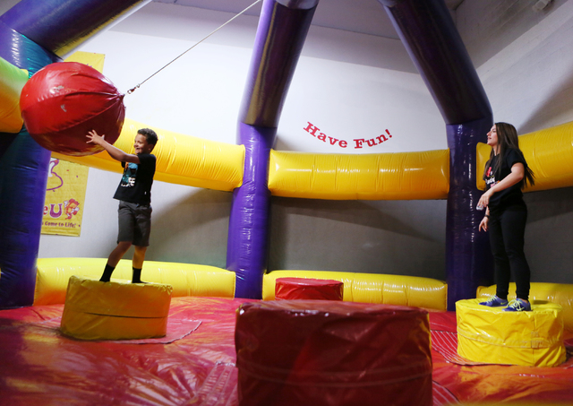 Jaylin Bohlen, 8, left, plays a wrecking ball game with staff member Alyssa Miele at BounceU Henderson Monday, March 31, 2014. The 1000 Stephanie Place, Suite 14, facility offers a variety of indo ...
