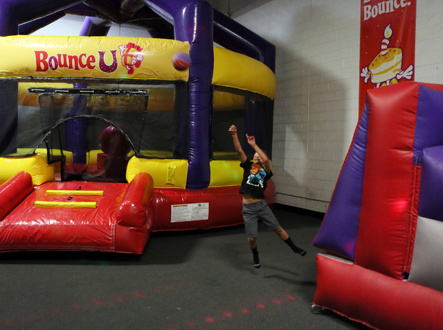 Jaylin Bohlen, 8, throws a basketball at BounceU Henderson Monday, March 31, 2014. The 1000 Stephanie Place, Suite 14, facility offers a variety of indoor bouncing obstacles as well as creative ca ...