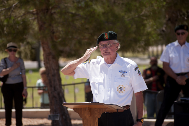 Retired U.S. Army Lt. Col. Al Hendley salutes during the playing of the National Anthem at the Southern Nevada Veterans Memorial Cemetery in Boulder City, Nev., on Memorial Day Weekend, Sunday, Ma ...